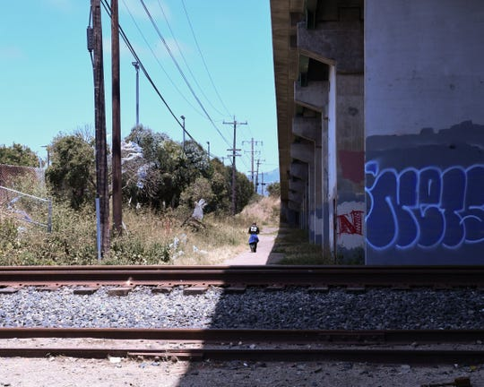 A man walks alongside the overpass, away from the homeless encampment by the rail road in Monterey County, where he he stays. June 12, 2019.