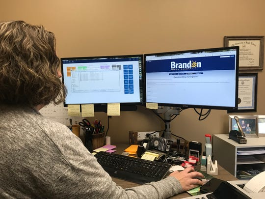 Brandon Finance Officer, Christina Smith, works on the Brandon website that will start accepting paperless billing requests starting in November.