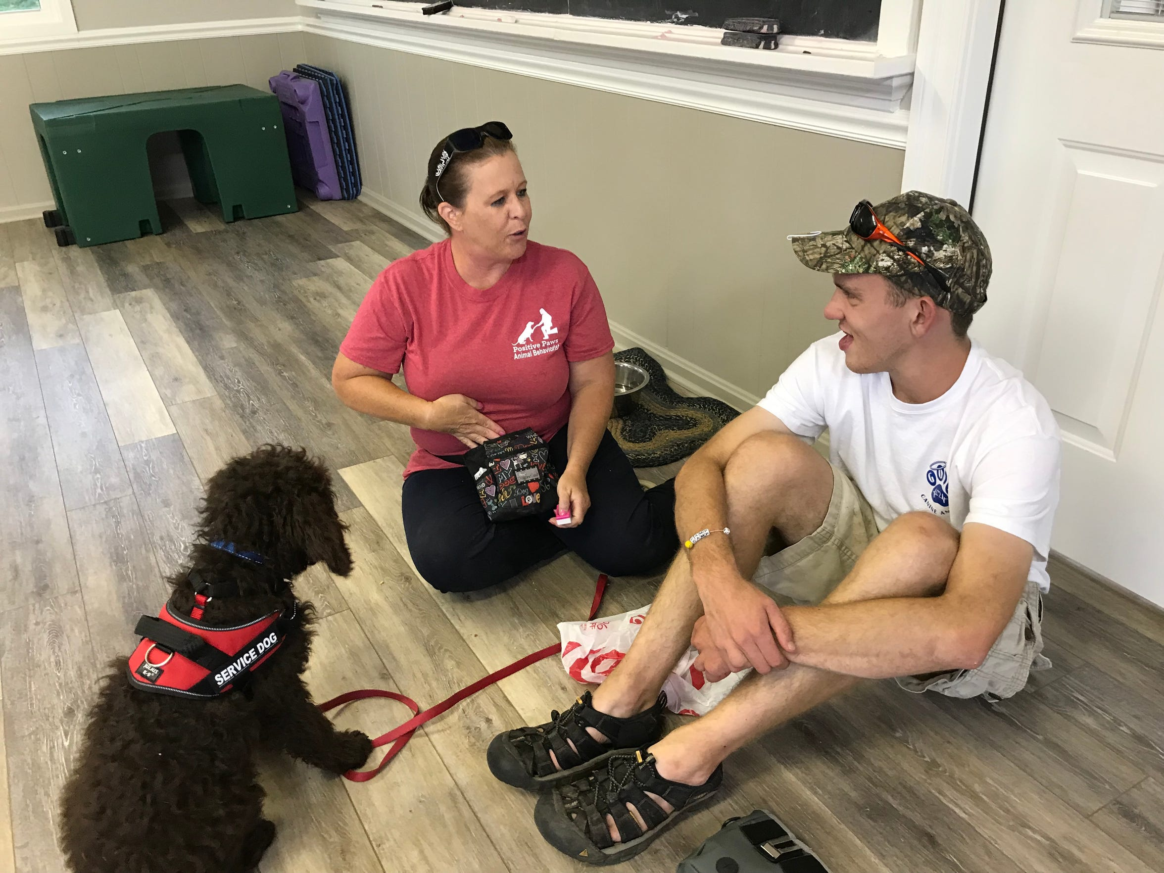 Stacey Payne, co-founder of God's Canine Angels in Stuarts Draft, Virginia, trains with Mcgregor Knemoller and his service dog Mace. Knemoller volunteers at Positive Paws, owned by Payne, four days a week as part of the Augusta County Regional Post High School Program.