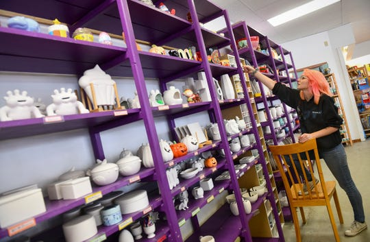 Jamie Stultz arranges art projects on shelves Friday, Oct. 4, 2019, at Art As You Like It in St. Cloud.