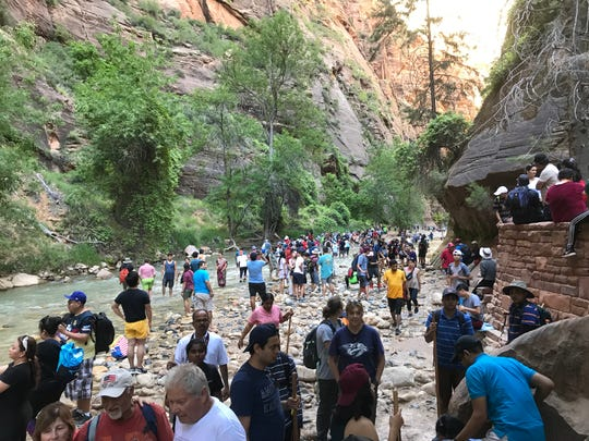 People crowd the trail known as The Narrows at Zion National Park over the summer.