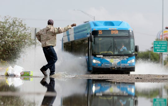 Dennis Billings of Northeast El Paso tries to hail a bus on a flooded Dyer Street on Friday morning, Oct. 4, 2019. Billings waited just off the sidewalk to not get splashed by passing vehicles.