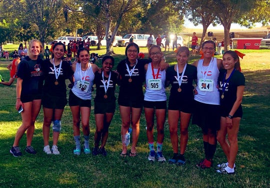The Ventura College women's cross country team celebrates winning the Bakersfield Invitational on Sept. 27.
