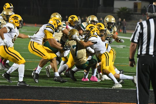 St. Bonaventure running back James Arellanes is engulfed by the Newbury Park defense during Thursday's game at Ventura College.