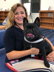 Millville High School Principal Stephanie DeRose holds her pet, Lily, who was named the school's pet therapy dog by the Millville Board of Education.