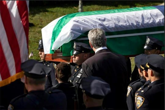 The casket bearing New York City police officer Brian Mulkeen is carried past New York Mayor Bill de Blasio into Church of the Sacred Heart, Friday, Oct. 4, 2019, in Monroe, New York. Authorities say Mulkeen, who lived in Yorktown Heights, New York, was fatally hit Sunday, Sept. 29, 2019, by two police bullets while struggling with an armed man in the Bronx. He is the second New York City officer killed by friendly fire this year.