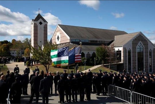 Police officers line the street in front of Church of the Sacred Heart, Friday, Oct. 4, 2019 in Monroe, New York, for the funeral service for New York City Police Officer Brian Mulkeen. Authorities say Mulkeen was fatally hit Sunday, Sept. 29, 2019, by two police bullets while struggling with an armed man in the Bronx. Mulkeen grew up in Monroe and lived in Yorktown Heights, New York. He is the second New York City officer killed by friendly fire this year.