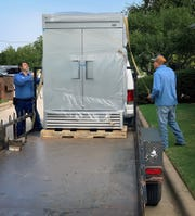 Jimmy Corona, left, and Nacho Mendoza from Wichita Restaurant Supply prepare to unload a large commercial refrigerator donated by the Leadershup Wichita Falls Class of 2019 to the Children's Aid Society.