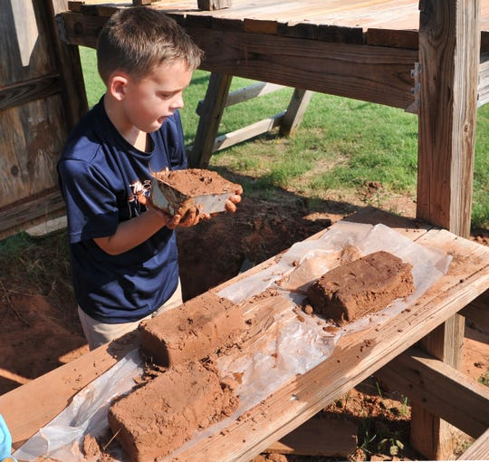 Koltin McCutcheon, 7, demonstrates Friday how he creates bricks out of dirt he got from the Lake Wichita area. The boy said seeing all the bricks he's made makes him happy. One day he hopes to build a house out of his handmade creations.