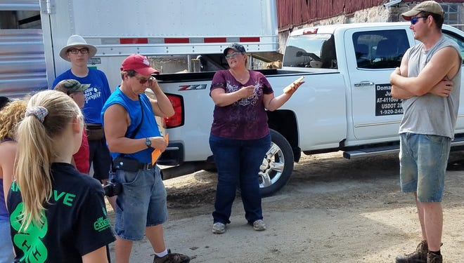 Becky Doman, center, of Watertown tells Dodge County 4-H members that the experience she gained in livestock and meat Judging while in 4-H has served her well in her livestock hauling and marketing business.