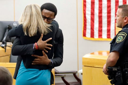 Botham Jean's younger brother Brandt Jean hugs convicted murderer and former Dallas Police Officer Amber Guyger after delivering his impact statement to her after she was sentenced to 10 years in jail, Oct. 2, 2019, in Dallas. Guyger shot and killed Botham Jean, an unarmed 26-year-old neighbor, in his own apartment last year. She told police she thought his apartment was her own and that he was an intruder.