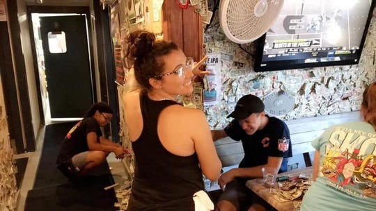 Bar employees taking down the thousands of bills that line the walls.