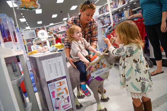Tiffany Fitzgerald and her daughter Eliza Fitzgerald, left, shop as Brooklyn Bonnell, 2,  checks out the displays with her mother Ashlan Bonnell, right, at Target in Leesburg, VA., Oct 4, 2019.  Disney and Target are teaming up and the first 25 Disney stores opened today.