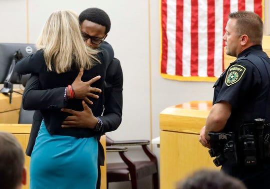 Brandt Jean, 18, hugs former Dallas police officer Amber Guyger, 31, on Oct. 2, 2019, in Dallas.