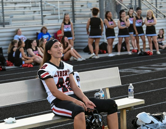 Liberty High School senior kicker Alexis Holliday sits on a bench near the cheerleaders, smiling with teammates after warming up before playing at Seneca in October.