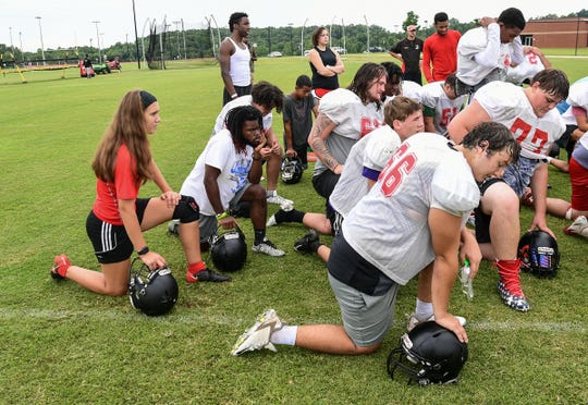Liberty High School senior kicker Alexis Holliday, left, with team listens to head coach Kyle Stewart during practice in August.