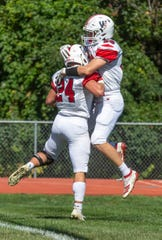 Wall's Matt Dolive (right) celebrates with teammate Matt DeSarno after DeSarno scored Wall's first touchdown in the Crimson Knights' 14-7 upset of Mater Dei Prep Saturday.