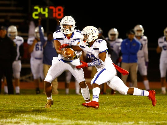Donovan Catholic QB Ryan Clark hands off to Jahdir Loftland during their game against Red Bank Regional in Little Silver Friday night, October 4, 2019.