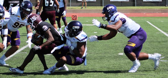 McMurry's Moise Fokomla (15) is corralled by Crusaders defenders on a first-half carry Saturday against Mary Hardin-Baylor. The No. 1 Cru easily defeated the War Hawks 79-0 in an American Southwest Conference game, giving up 54 total yards.