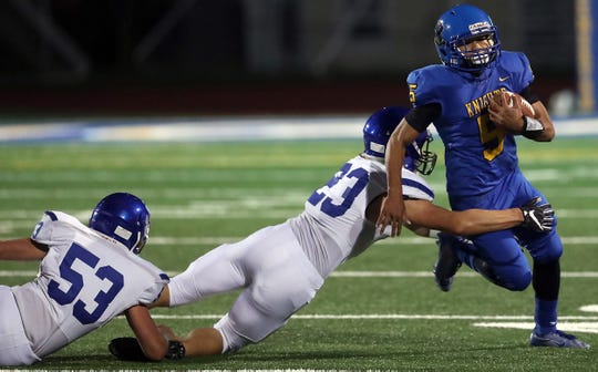 North Mason's Josh Simons (53) and Mason Shumaker (23) try to bring down Bremerton's Jayden Quenga (5) during their game on Friday, Oct. 4, 2019.
