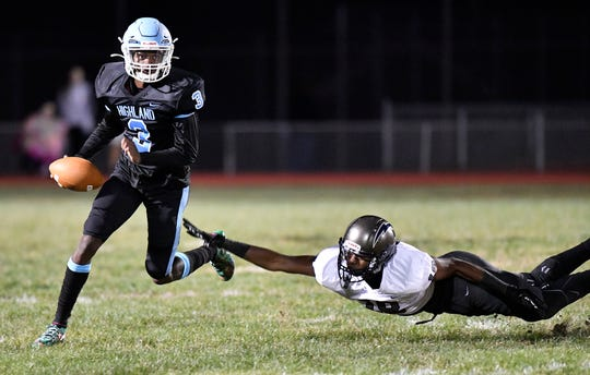 Highland quarterback Javon Holley evades a tackle during Friday night's football game against visiting Timber Creek.