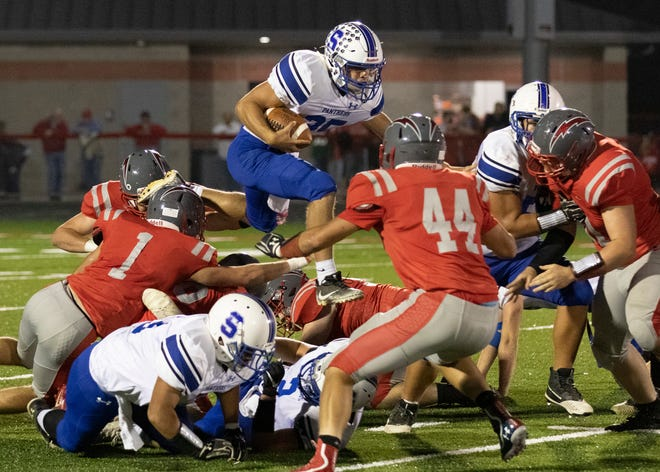 Southeastern quarterback Lane Ruby jumps over defenders in a 54-34 win over Piketon Friday night in Piketon, Ohio.