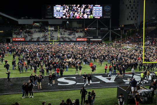 Cincinnati Bearcats fans storm the field after the 27-24 win against the UCF Knights, Friday, Oct. 4, 2019, at Nippert Stadium in Cincinnati.
