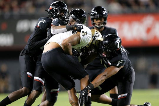 The Cincinnati Bearcats defense gang tackles UCF Knights wide receiver Gabriel Davis (13) in the fourth quarter of a college football game, Friday, Oct. 4, 2019, at Nippert Stadium in Cincinnati.