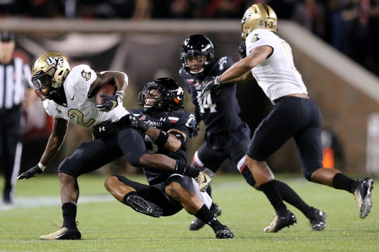 Cincinnati Bearcats safety Darrick Forrest (5) tackles UCF Knights running back Otis Anderson (2) in the first quarter of a college football game, Friday, Oct. 4, 2019, at Nippert Stadium in Cincinnati.