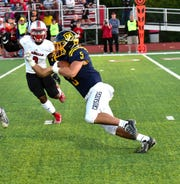 Moeller's TJ Rotello (5) shifts into high gear for a Crusaders' first down in GCL-South action against La Salle, Oct. 4, 2019.