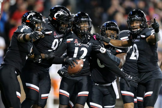 Cincinnati Bearcats cornerback Ahmad Gardner (12) is congratulated after scoring on an interception return for a touchdown in the third quarter of a college football game, Friday, Oct. 4, 2019, at Nippert Stadium in Cincinnati.