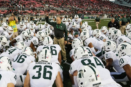 Michigan State head coach Mark Dantonio huddles with players during warmups before the Ohio State game at Ohio Stadium in Columbus, Ohio, Saturday, Oct. 5, 2019.