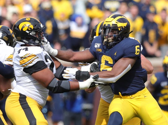 Michigan Wolverines linebacker Josh Uche rushes against Iowa Hawkeyes offensive lineman Tristan Wirfs during the first half Saturday, Oct. 5, 2019 at Michigan Stadium in Ann Arbor.