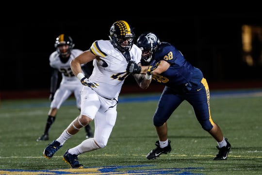 Port Huron Northern defensive end Braiden McGregor rushes against Fraser offensive lineman Anthony Merlo during the first half.