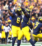 Michigan linebacker Josh Uche (6) and safety Josh Metellus celebrate a fumble recovery by defensive back Ambry Thomas during the first half on Saturday, Oct. 5, 2019, at Michigan Stadium.