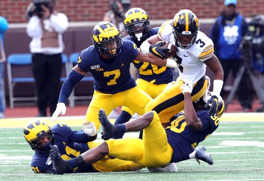 Michigan defenders tackle Iowa wide receiver Tyrone Tracy Jr. during the first half of U-M's 10-3 win on Saturday, Oct. 5, 2019, at Michigan Stadium.