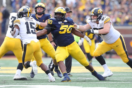 Offensive lineman Tyler Linderbaum, scrambles as running back Tyler Goodson (15) looks for room during the second half of Iowa's 10-3 loss at Michigan Stadium.