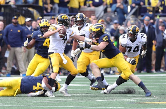 Michigan linebacker Cameron McGrone, bottom, and defensive linemen Michael Danna (4) and Aidan Hutchinson pressure Iowa quarterback Nate Stanley during the second half of U-M's 10-3 win on Saturday, Oct. 5, 2019, at Michigan Stadium.