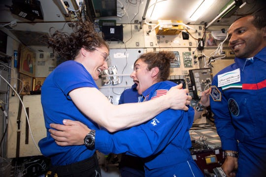 In this photo made available by NASA astronaut Jessica Meir on Sept. 29, 2019, Christina H. Koch, left, and Meir greet each other after Meir's arrival on the International Space Station. On Friday, Sept. 4, 2019, NASA announced that the International Space Station's two women will pair up for a spacewalk on Oct. 21 to plug in new batteries.