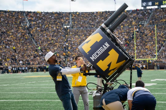 Former Michigan football player Charles Woodson enjoys firing a pneumatic t-shirt canon during a timeout in the first half of Saturday's game. Later in the evening, he was inducted into the Michigan Sports Hall of Fame.