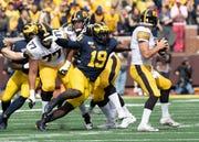 Michigan defensive lineman Kwity Paye sacks Iowa quarterback Nate Stanley (4) in the first quarter.