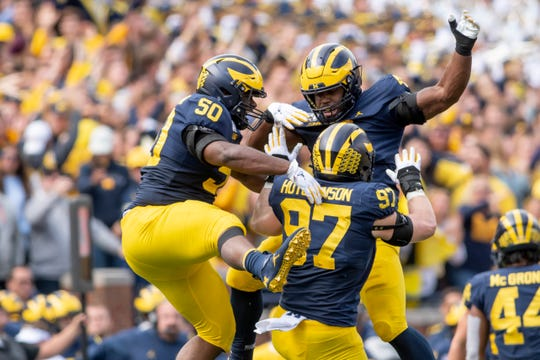 From left, Michigan defensive linemen Michael Dwumfour, Michael Danna and  Aidan Hutchinson celebrate after a sack late in the fourth quarter.