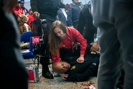 Boxer Ivana Habazin helps her trainer Bashir Ali after he was punched by a man and fell to the ground before Habazin's weigh-in last month in Flint. Ali was sent to McLaren Hospital in Flint to be treated. A man faces charges for the punch.