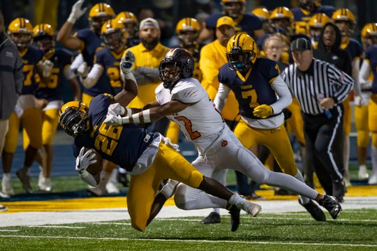 Dearborn Fordson's KeyShawn Smith (26) is tackled by Belleville's Ronald Jackson Jr. (22) in the first half on Friday.
