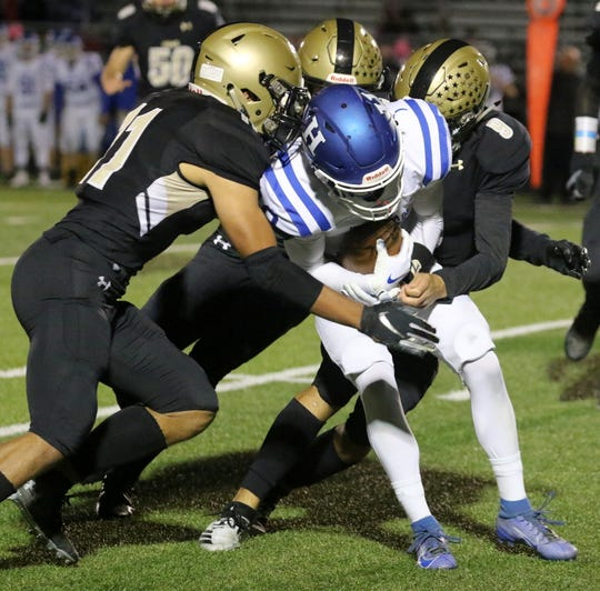 Three Corning players combine to tackle Ryan Scott of Horseheads on Oct. 4, 2019 at Corning Memorial Stadium.