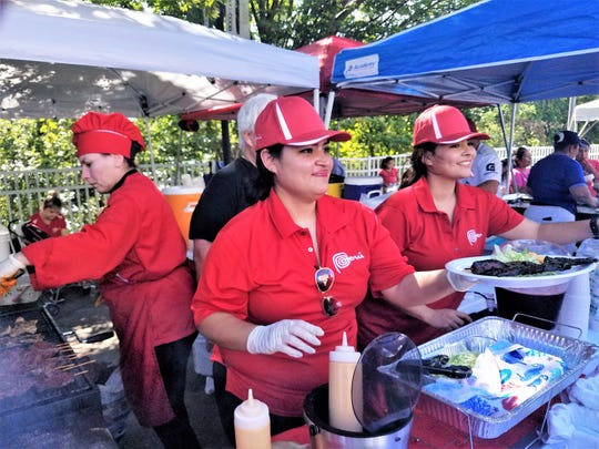 A group of Peruvian cooks serves skewers of grilled beef at the 2018 Fiesta Evansville.