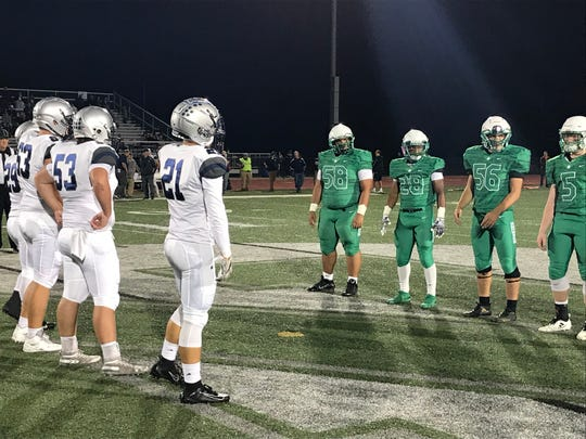 Captains from North and Reitz meet before Friday night's kickoff.