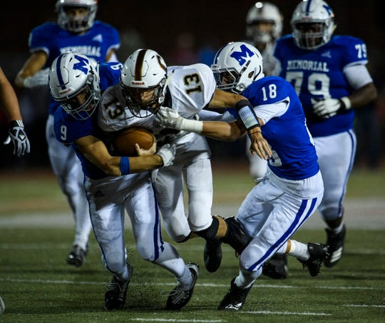 Memorial's Josh Russell (9) and John Shea (18) take down Central's Collins Turner (13) during the fourth quarter Oct. 4 at Enlow Field. Both teams are vying for the SIAC title.