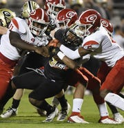 Greer's Ian Jackson (9)  is stopped by a host of Greenville defenders Friday night at Dooley Field in Greer.