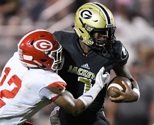 Greer quarterback Raheim Jeter (7) is stopped by Greenville's Terrance Gist (12) Friday, October 4, 2019, at Dooley Field.